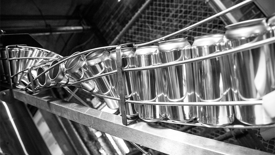 aluminum beer cans twisting on metal canning machinery