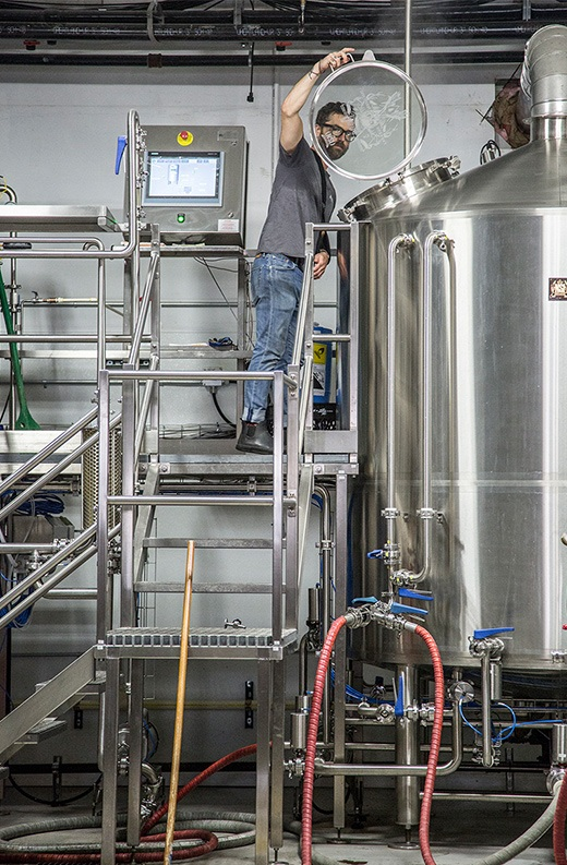 male worker standing on metal platform inspects interior of stainless steel fermentation tank