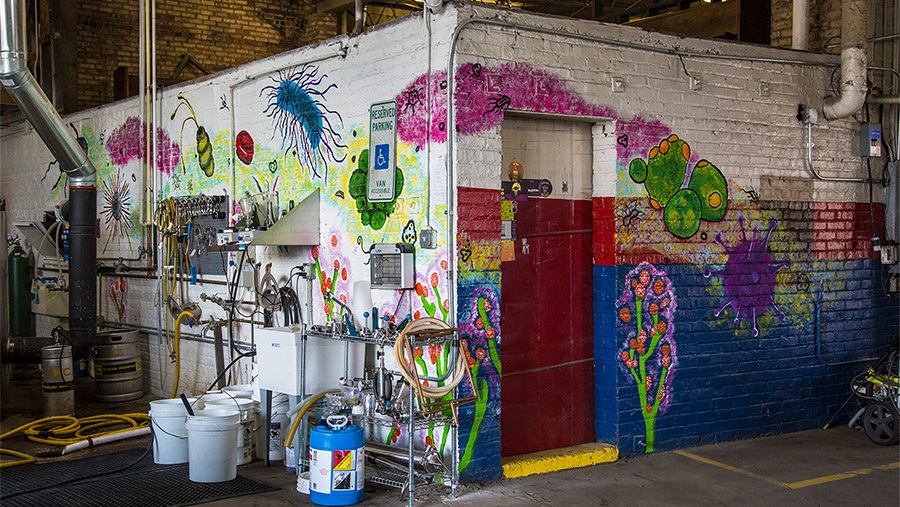 buckets, chemicals, cleaning and maintenance equipment against colorful graffiti-covered brick wall in a warehouse