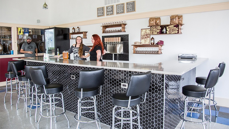 modern taproom with leather stools surrounding mosaic-tile bar with two smiling female bartenders