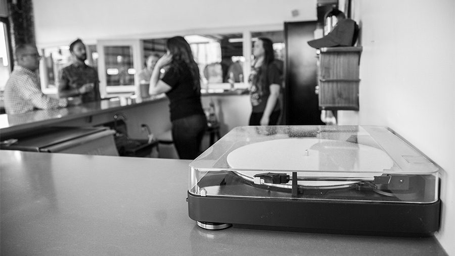 contemporary record player on a bar top with bar staff and patrons in the background
