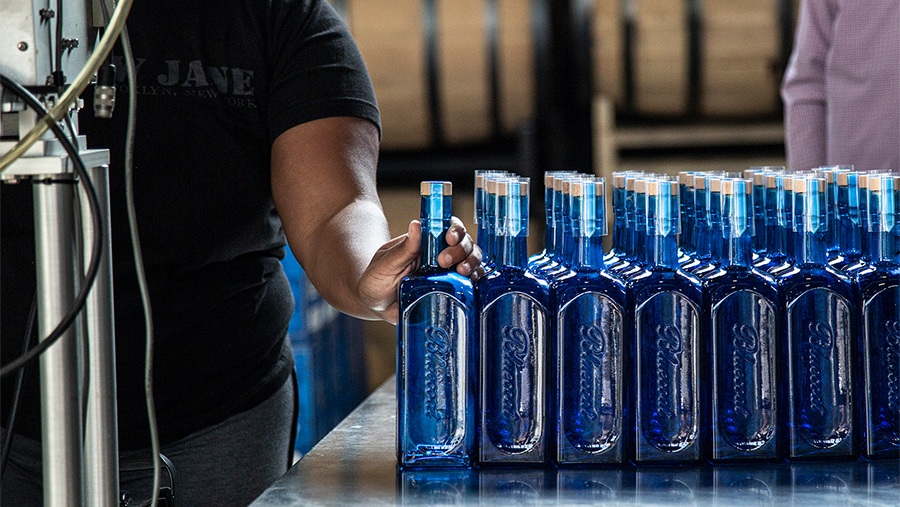 rows of blue glass gin bottles being placed on a table by worker