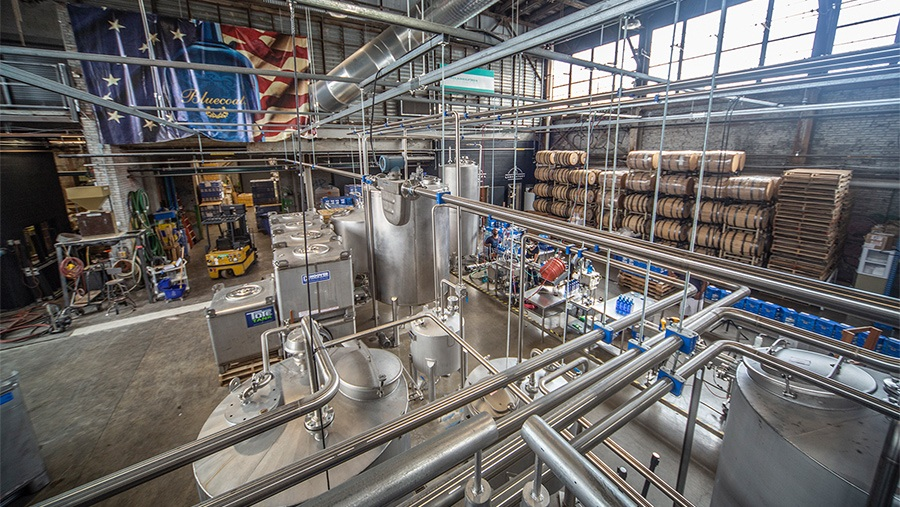 warehouse interior with extensive stainless steel tubing, steel distillation equipment and stacks of wooden barrels