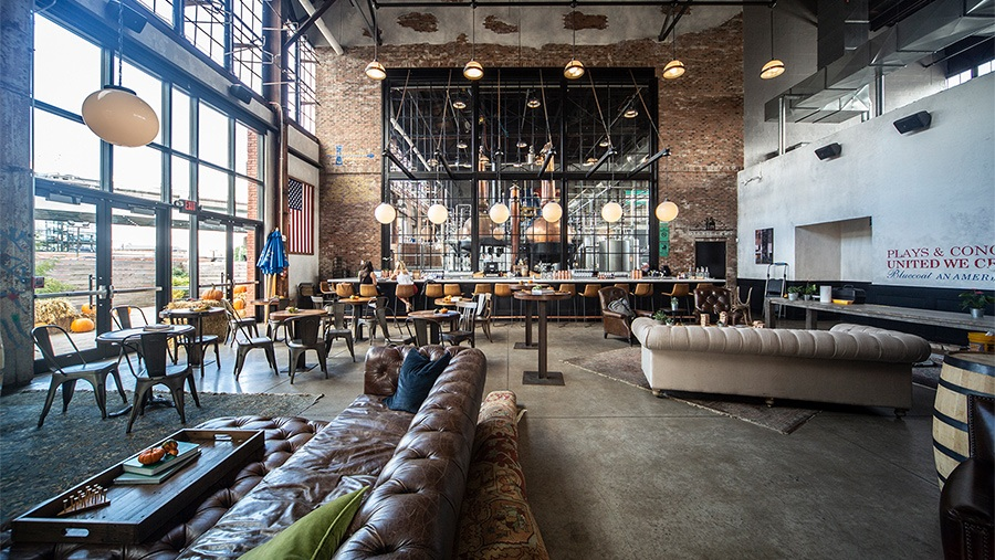 light shines through large glass windows into luxury warehouse taproom with leather seating, exposed brick walls and modern light fixtures