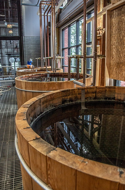 water-filled wooden tanks with copper plumbing in a warehouse