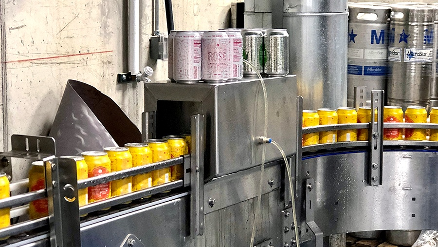 yellow aluminum cans move through automated metal machinery into a washer that cleans and sanitizes the cans