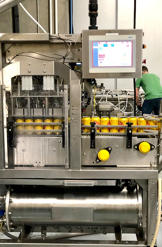 yellow aluminum cans being filled with cider as they move through automated metal machinery with a digital screen
