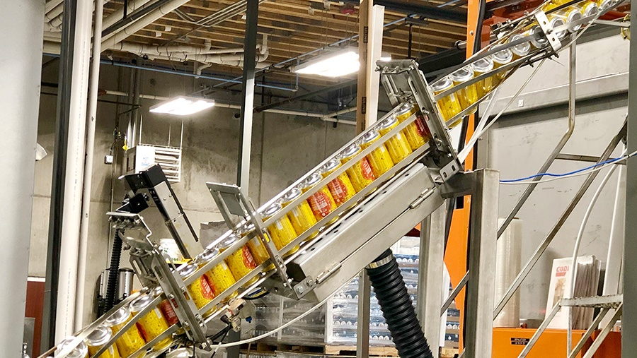 yellow cans being rotated 180 degrees by extending large metal can conveyor machinery in a warehouse