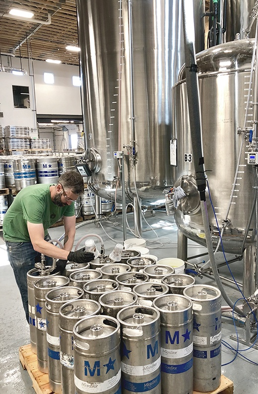 bearded man in green shirt filled half-sized aluminum kegs with cider from tubing  directly from stainless steel tanks