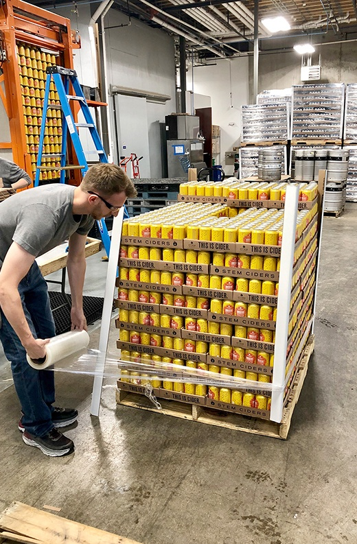 man wraps plastic around a pallet of yellow aluminum cider cans being prepared for distribution in a warehouse
