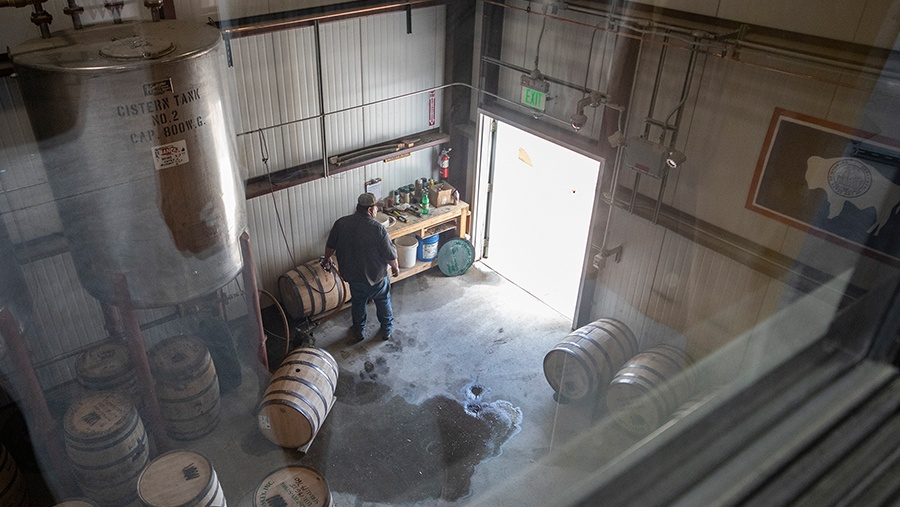 looking down on man in a garage filling wooden barrels with whiskey from a large steel vat on stilts