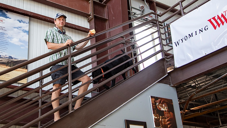 Co-Founder David Defazio, fair skin man in baseball cap and button shirt, stands with his black lab dog on a brown metal staircase