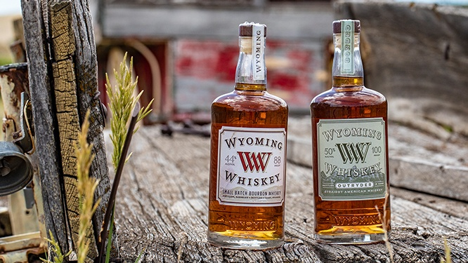 two bottles of wyoming whiskey on a wooden truckbed