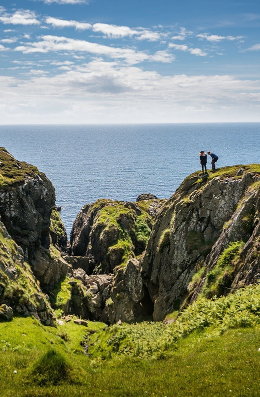 two people stand near a cliff edge on a rugged Scottish coastal terrain