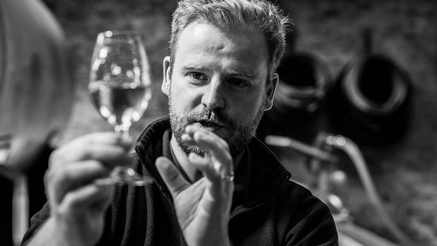 bearded man gazes at the snifter of whisky in his hand as he describes