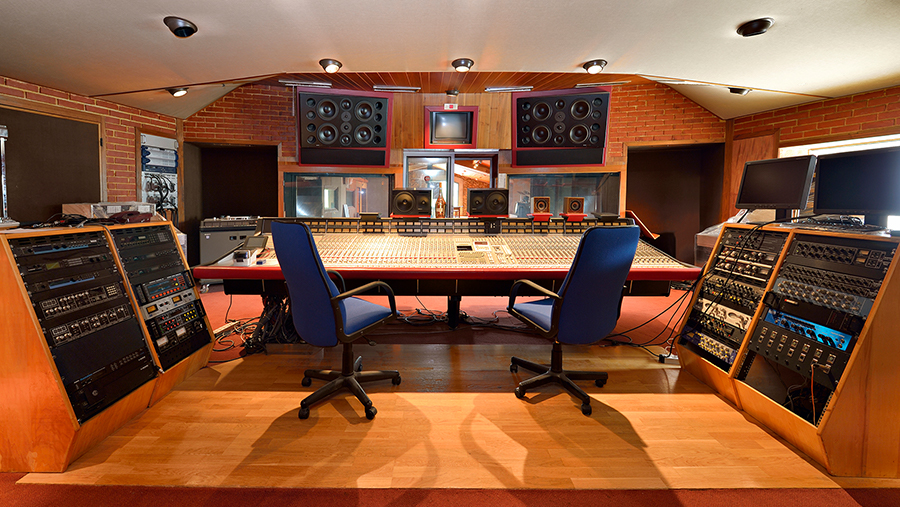 Brick-walled room filled with a large mixing board and other music recording equipment
