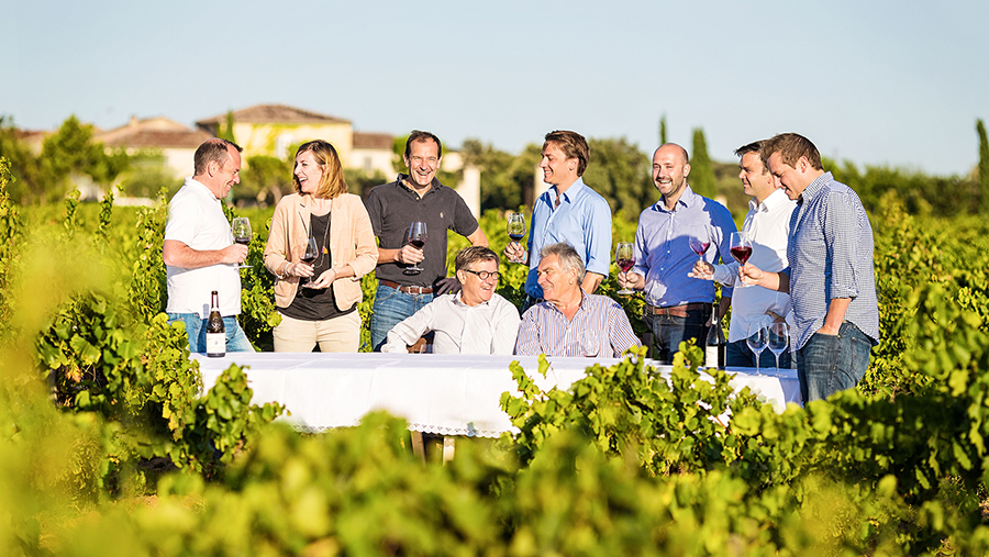 Group of family members drinking red wine gather around for an outdoor table at a vineyard