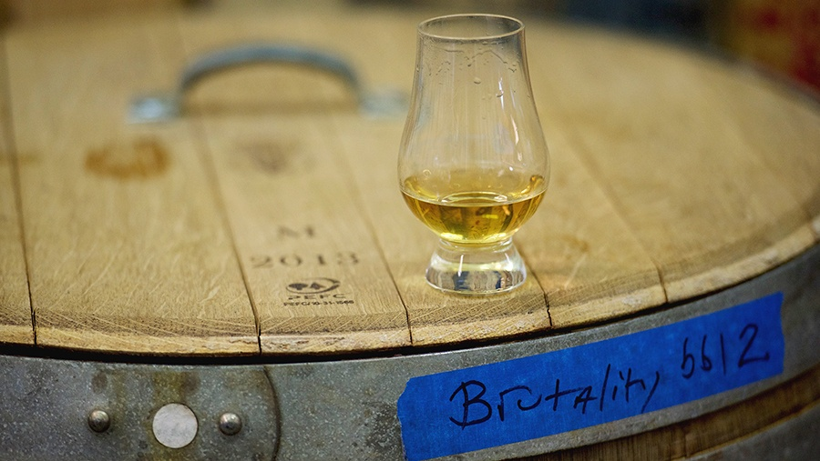 a snifter of golden whiskey sits atop a wooden barrel labeled Brutality