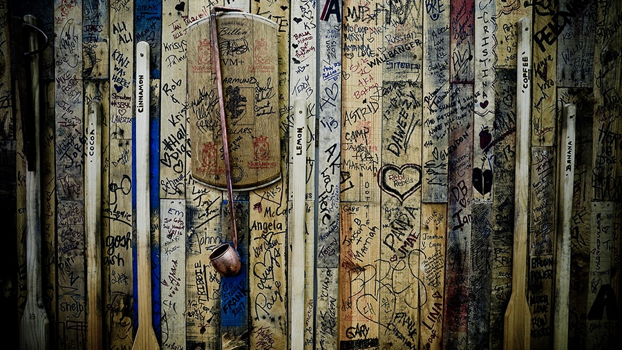 handwritten signatures from guests cover a wooden wall where distillery tools are stored