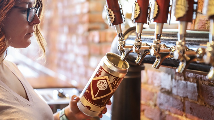 employee at Odell's Rino Taproom pours beer into a crowler from a tap