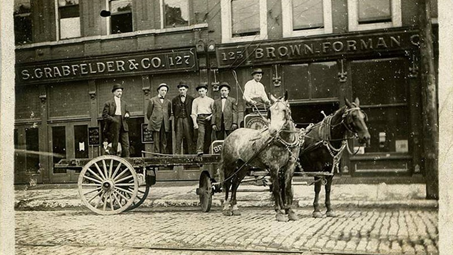 men standing on horse-drawn buggy on cobblestone street