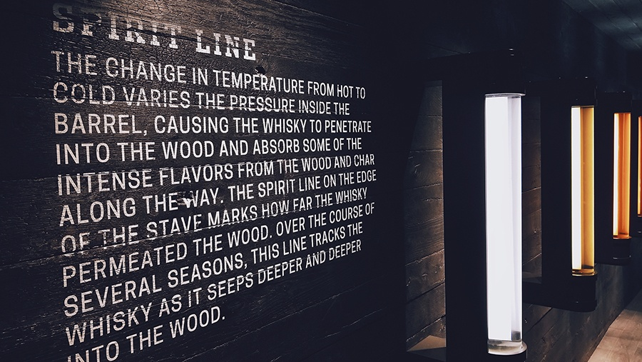educational description on a black wooden wall explaining whisky barrel aging effects