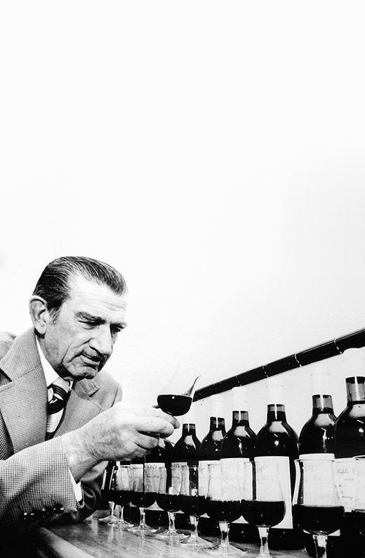 Penfold's original Chief Winemaker, Max Schubert, visually inspects wine quality from a row of snifters filled from a variety of bottles