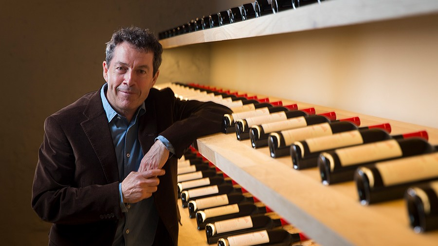 Penfold's Chief Winemaker, Peter Gago, leans one of many shelves lined with bottles of red wine