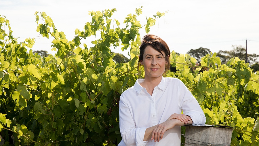 Penfold's Senior Winemaker, Steph Dutton, leans on a wooden vineyard post in front of a wall of grape vines and leafs