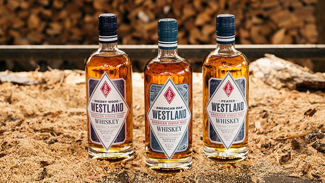 Bottles of Westland Sherry Wood, American Oak and Peated whiskies on a bed of sawdust